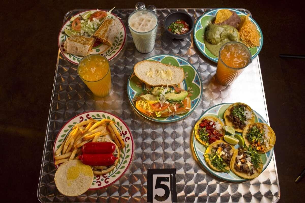 From left, clockwise, burrito, horchata, mole verde plato, mango, taquiza mixta, salchi-burger, melon and veggie torta, center, at Taqueria La Macro