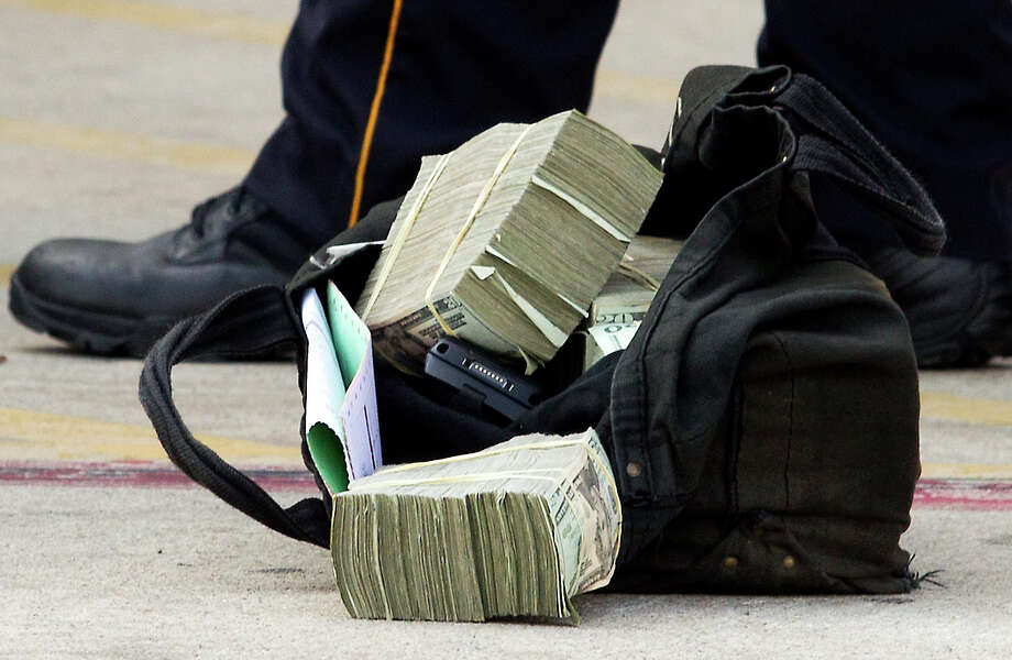 A bag of money is left in the parking lot outside Walgreens after a armored car was robbed off of Little York and the Eastex freeway on Friday, Sept. 6, 2013, in Houston. Photo: J. Patric Schneider, For The Chronicle / © 2013 Houston Chronicle