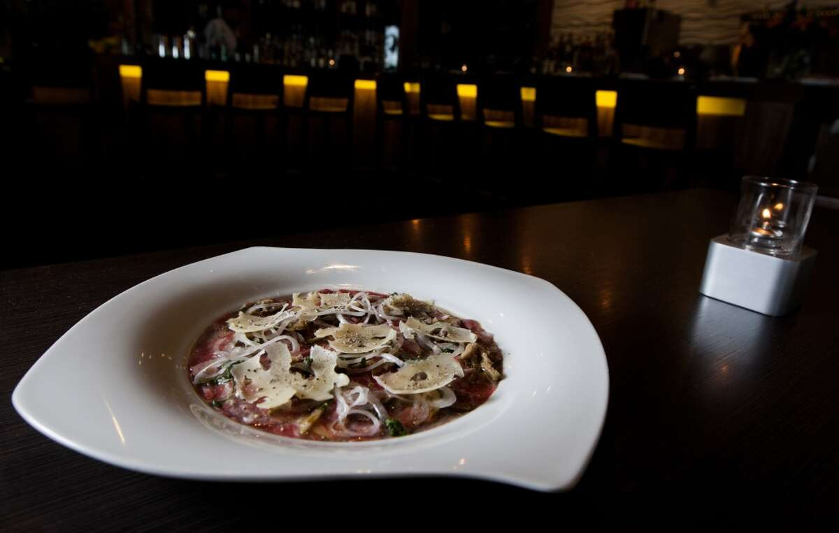 Beef-heart carpaccio with parmesan cheese, shallots, olives, and caper berries at the Cove Cold Bar. ( J. Patric Schneider / For the Chronicle )