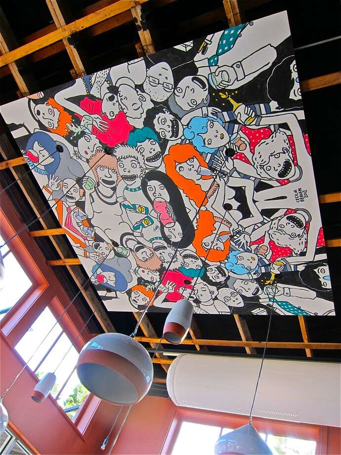 The cartoony murals of Cecilia Beaven decorate the ceiling of Cuchara.