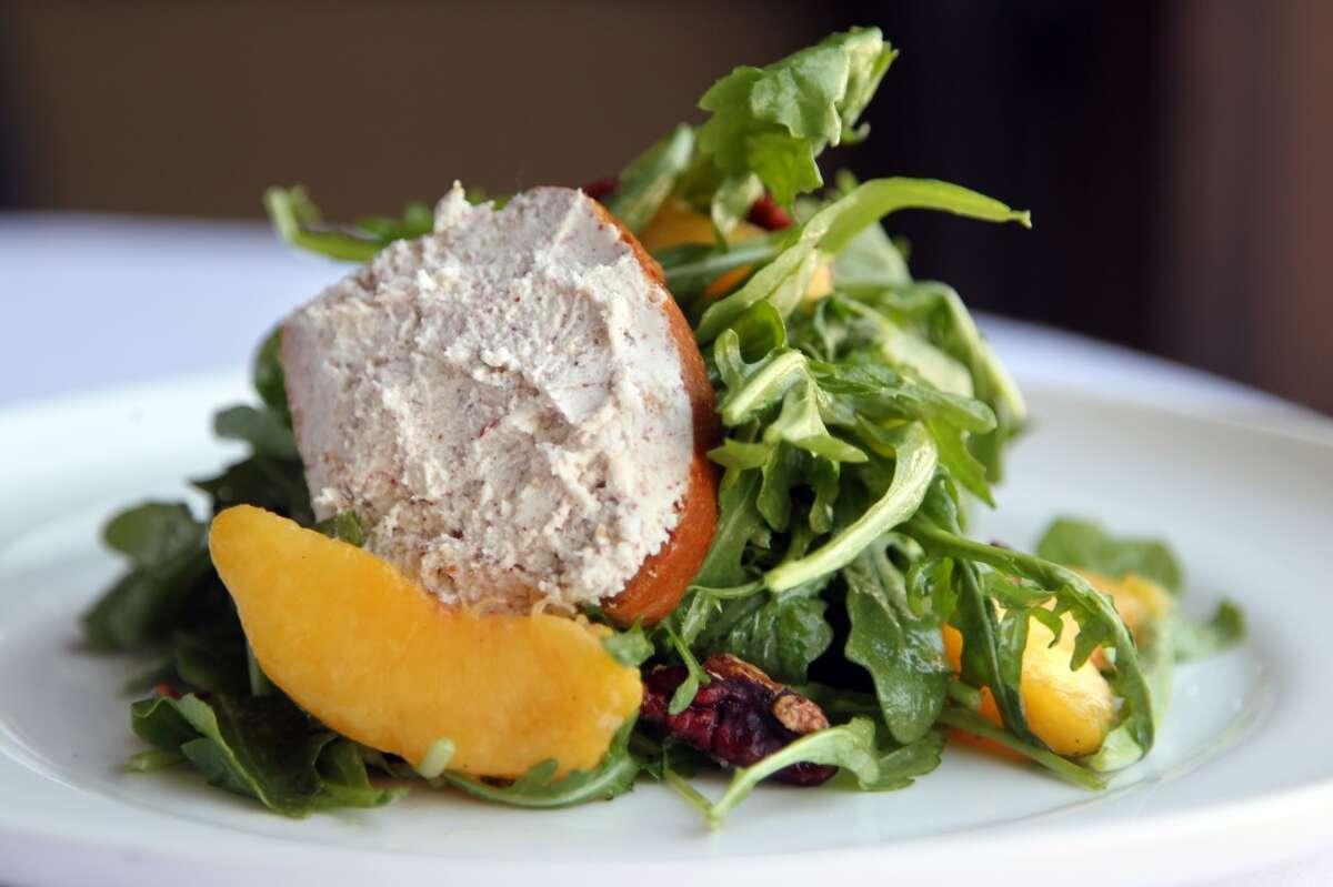 An Arugula Salad, peach vinaigrette, peaches, candied pecans, pink peppercorn, goat cheese toast at Haven