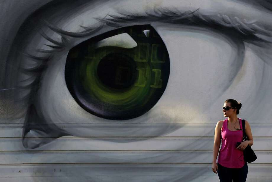 A wall eyeballs a woman in Athens. Photo: Petros Giannakouris, Associated Press