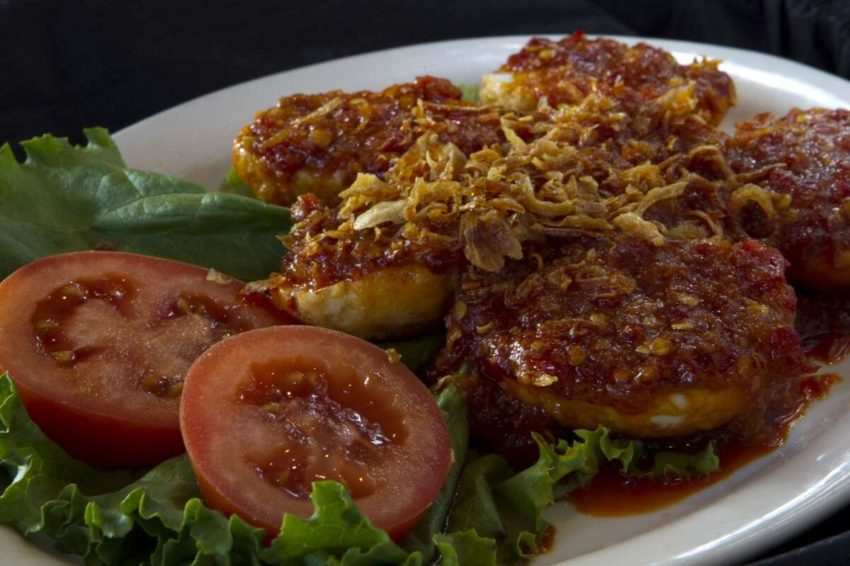 A dish of Telor Balado, fried whole eggs topped with a spicy sauce, is shown at Rice Bowl Indonesian