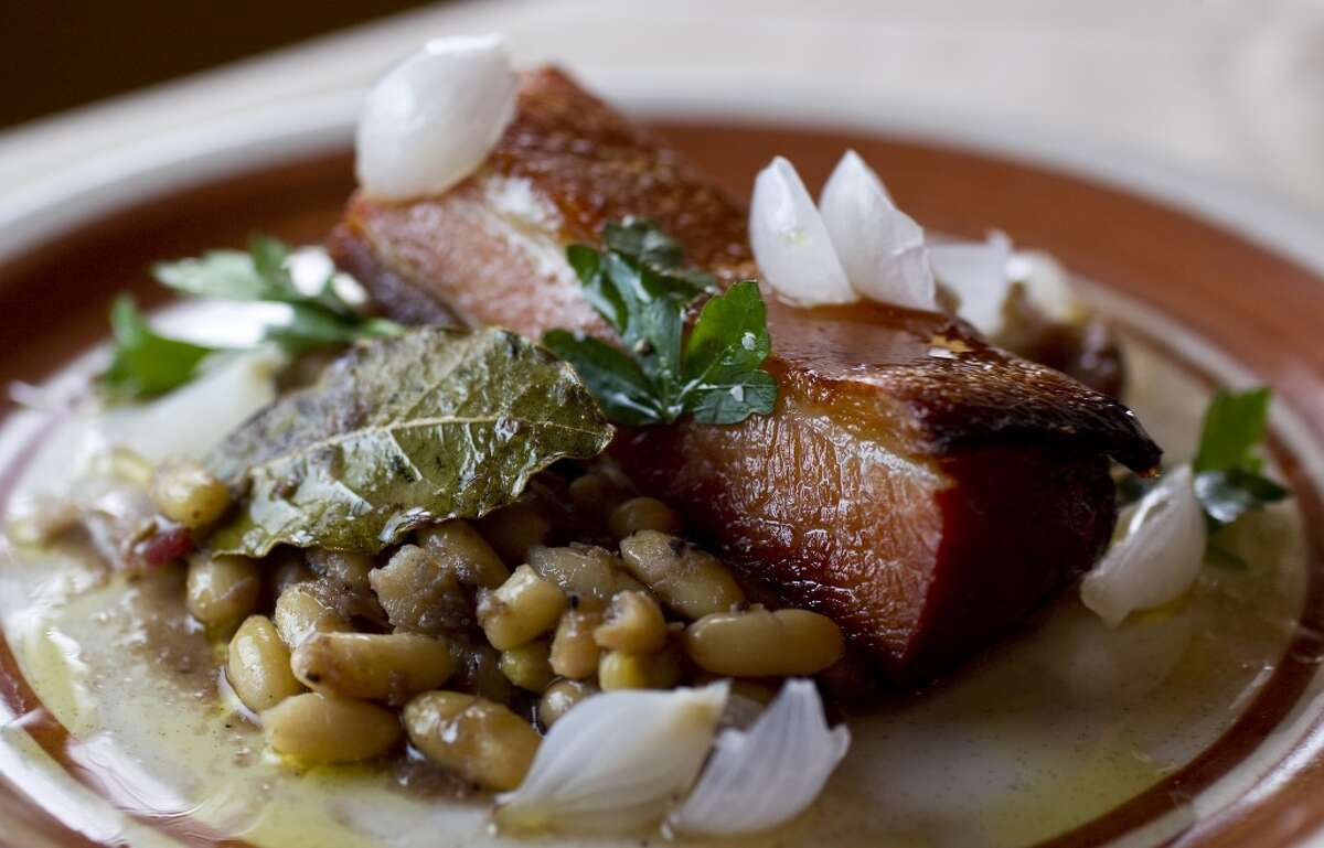 """The """"Pork and Beans"""", crispy pork belly, white bean ragout, duck rillette, and pancetta served at Roost"""