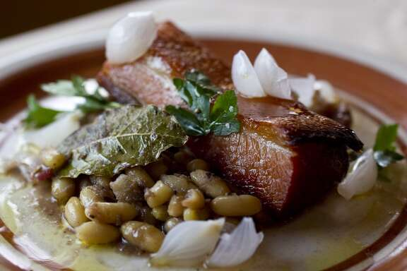 "The ""Pork and Beans"", crispy pork belly, white bean ragout, duck rillette, and pancetta served at Roost"