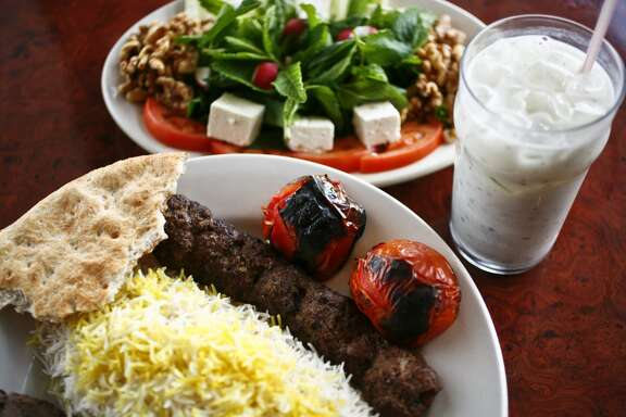 The Sultani, a skewer of beef Kubideh and a skewer of beef Barg along with white rice, the Special Herb Plate and a cup of Doogh, a yogurt drink, at Kasra