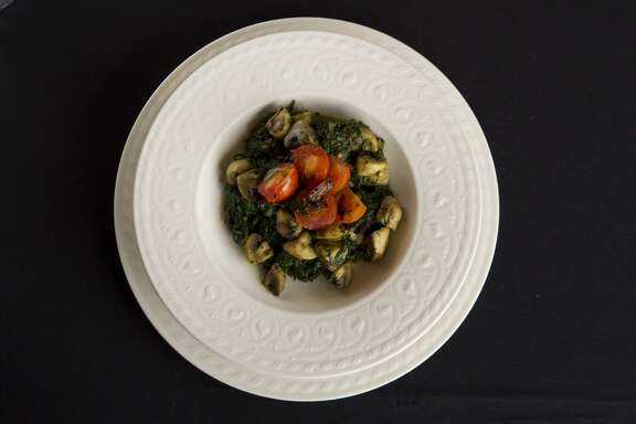 A bowl of spinach with mushrooms and tomatoes at Kiran's