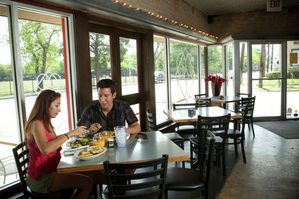Erika Montalvo, left, and Edward Galvez eat lunch in the dining room at Paulie's.