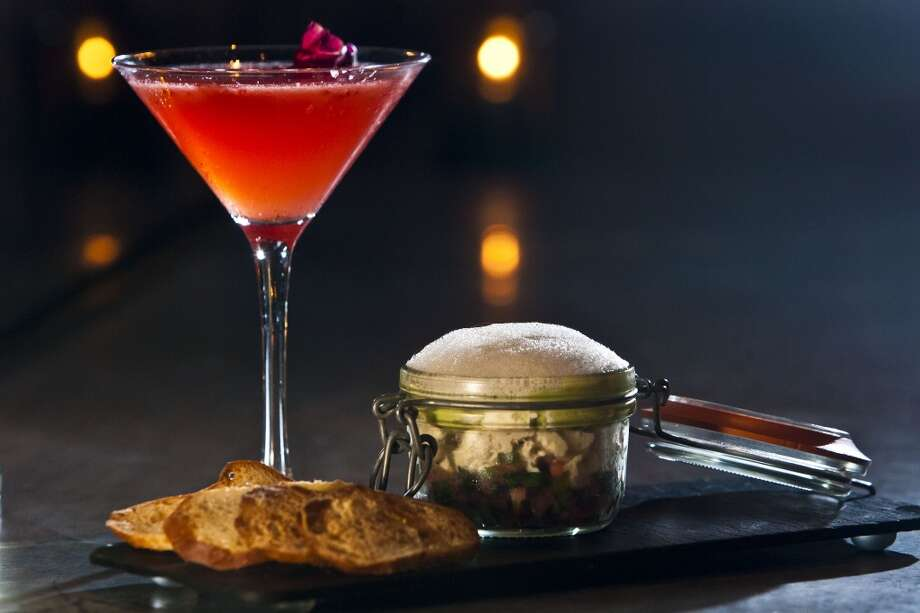 """The Blessing,"" made with Sobieski vodka, strawberry, pomegranate juice, lime juice, and garnished with a flower - with the ""Contained Decadence"" of ""crab and avocado,"" made with lime, cilantro, an olive oil emulsion served in a glass jar with a side of brioche toast, at the bar at Philippe Restaurant. Photo: Patrick T Fallon, Houston Chronicle"