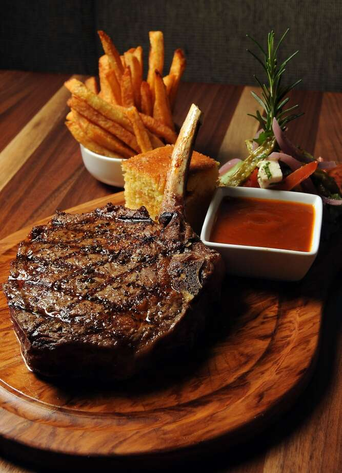 The cowboy steak:  16 oz bone-in grilled rib eye, cactus salad, cornbread cake, BBQ sauce and fries at Philippe Restaurant. Photo: Dave Rossman, For The Chronicle