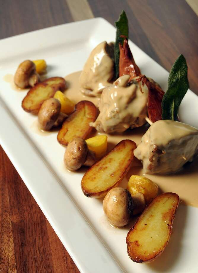 "The pig in a ""blanket"" : sage + cream-braised pork shoulder with mushrooms + Fingerling potatoes and shallot confit at Philippe Restaurant. Photo: Dave Rossman, For The Chronicle"
