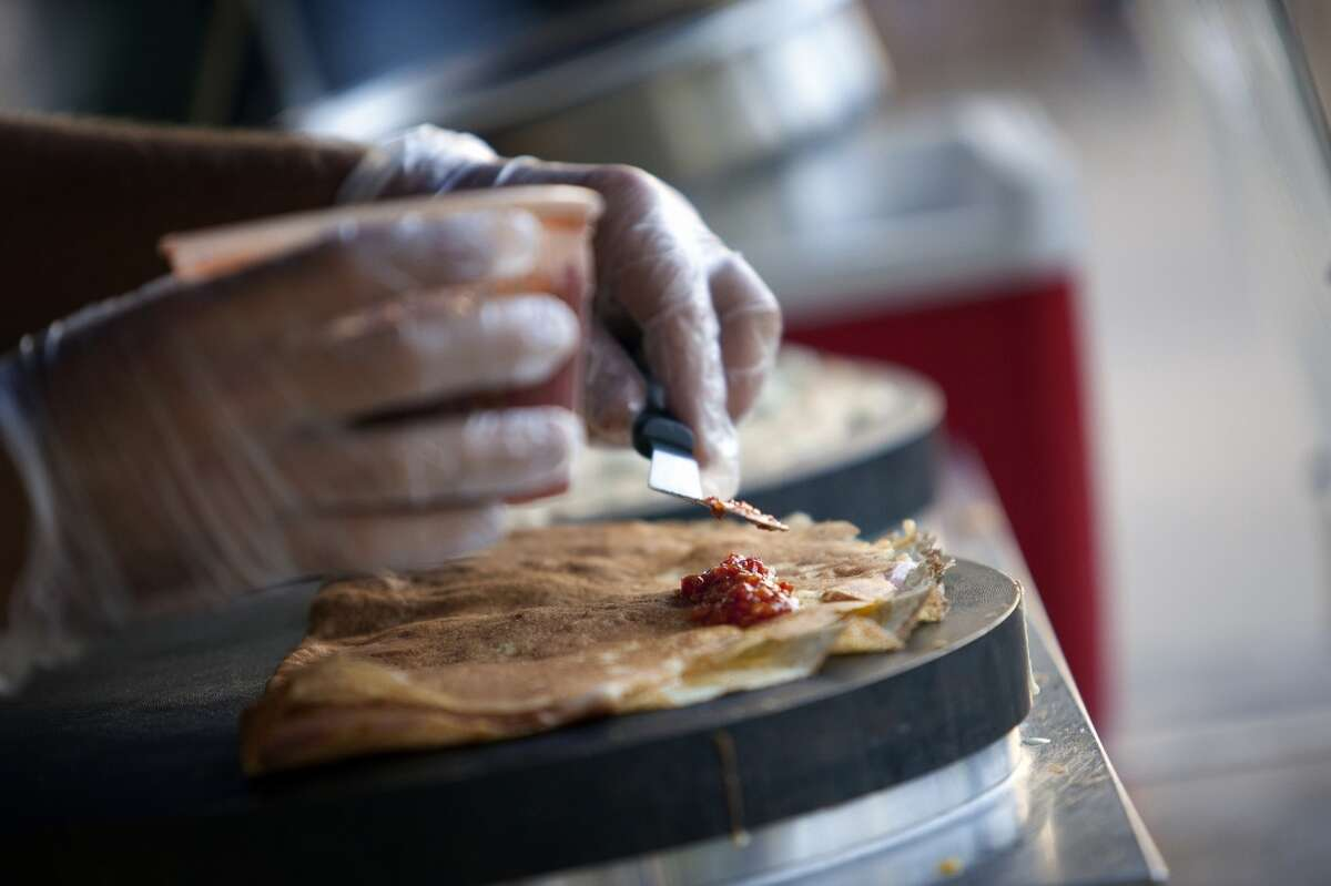 """""""Buffalo Sean"""" Carroll of Melange Creperie spreads a chili paste over a finished crepe."""