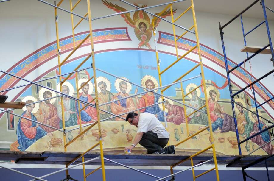 Dhimitri Cika, a professional icon painter, works on hanging his painting of the last supper on the south wall of St. Dimitrie Orthodox Church in Easton. Cika has undertaken the job of painting the icons for all four walls of the church which moved from Bridgeport to Easton a few years ago. the church is hosting its annual festival this weekend. Photo: Autumn Driscoll