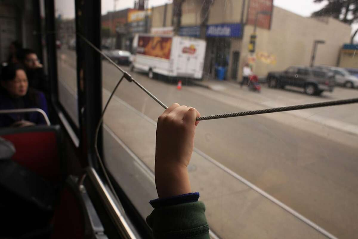 Ben Easter, 4, pulls the wire letting the MUNI driver know where his stop is in San Francisco, Calif.