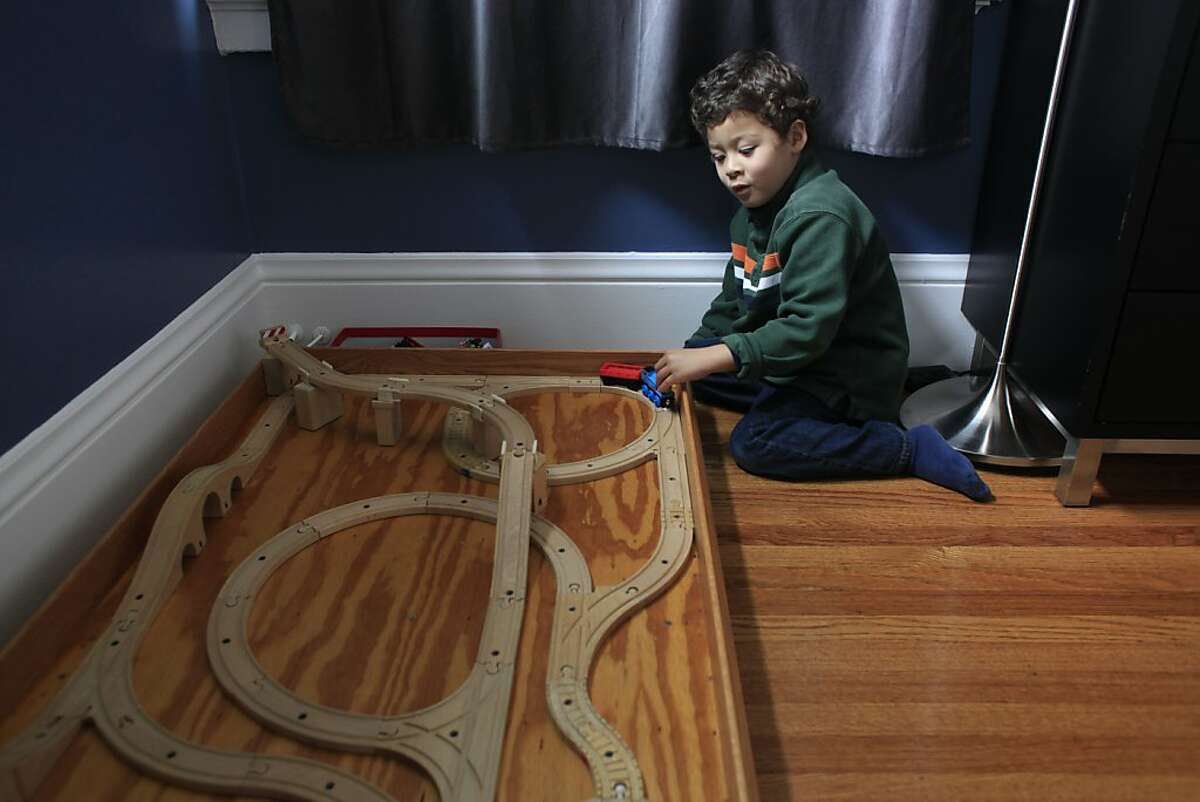 After spending the morning on the MUNI train with his grandmother, Ben Easter, 4, plays with his toy train set at home in San Francisco.