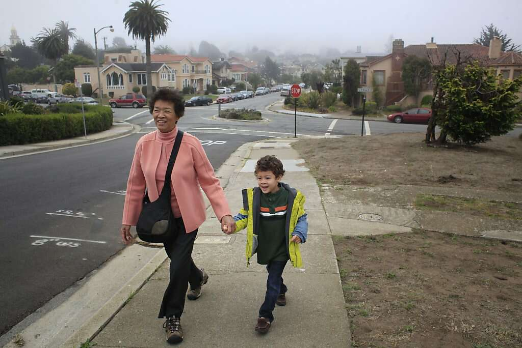 Ben Easter, 4, and his grandmother Maria Kwan walk to catch the MUNI train near their home San Francisco, Calif.