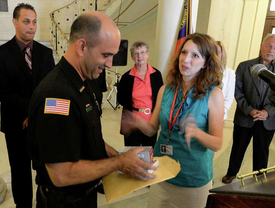 Schenectady County Sheriff Dom Dagastino receives nicotine patches and gum from Erin Sinisgalli of the Center for Smoking Cessation Thursday, Sept. 5, 2013, as part of a voluntary initiative by some of City Hall's workers and local politicians to quit smoking. The no-smoking initiative and the announcement of a Health Fair in Schenectady was the subject of a press briefing held by Schenectady Mayor Gary McCarthy took place in the Rotunda of City Hall in Schenectady, N.Y.  ( Skip Dickstein/Times Union ) Photo: Skip Dickstein / 00023775A