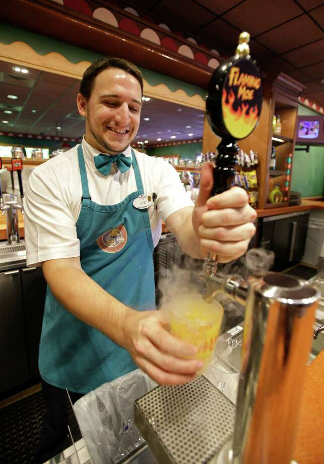 "Lee Phillips serves a Flaming Moe, a non-alcoholic beverage, at ""The Simpson's"" themed Moe's Tavern at Springfield USA at Universal Orlando in Orlando, Fla. Built around ""The Simpsons""ride that opened in 2008, the new zone is heavy on the tasty-yet-unhealthy food featured on the show. (AP Photo/John Raoux) Photo: Associated Press"