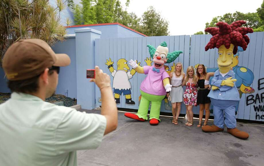 "A park employee takes a photo of guests with characters from the animated series ""The Simpson's"" at Springfield USA at Universal Studios Florida, Thursday, Sept. 5, 2013, in Orlando, Fla. Built around ""The Simpsons"" ride that opened in 2008, the new zone is heavy on the tasty-yet-unhealthy food featured on the show. (AP Photo/John Raoux) Photo: Associated Press"
