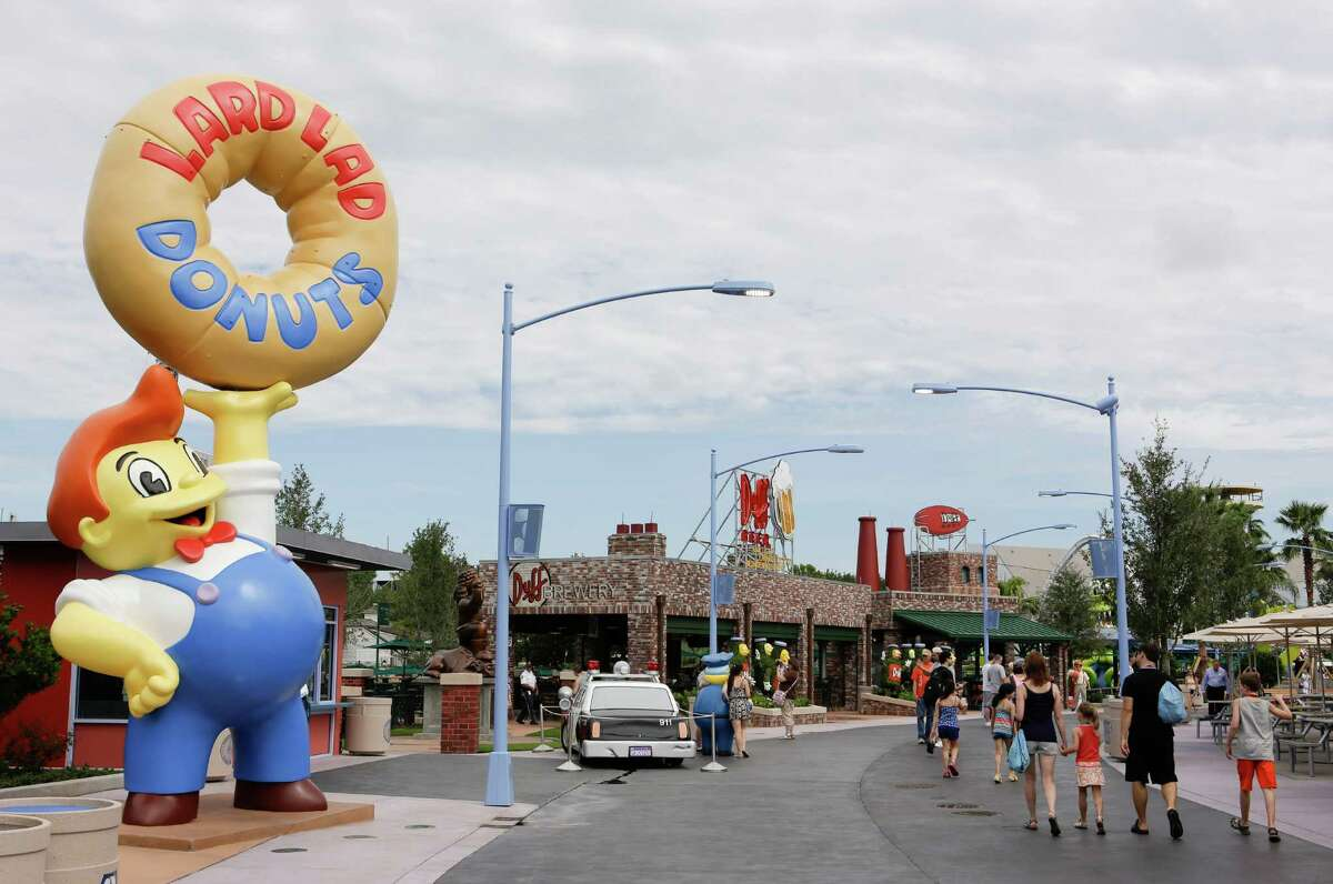 This photo shows park guests by Lard Lad Donuts, left, and Duff Beer Gardens at the Simpson's themed Springfield USA at Universal Studios Florida in Orlando, Fla. Built around
