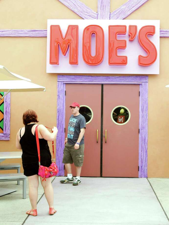 "Guests snap photos at the entrance to Moe's Tavern in ""The Simpson's"" themed Springfield USA at Universal Orlando in Orlando, Fla. Built around ""The Simpsons"" ride that opened in 2008, the new zone is heavy on the tasty-yet-unhealthy food featured on the show. (AP Photo/John Raoux) Photo: Associated Press"
