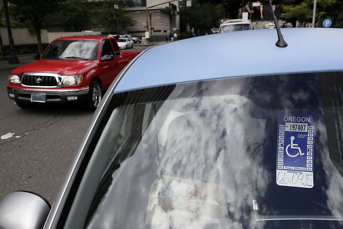In this Sept. 3, 2013, photo, a handicapped parking tag hangs from the rearview mirror of a car parked at a metered parking spot in Portland, Ore. As the number of vehicles displaying a disabled placard has soared with an aging population and loosened eligibility standards, cities are seeing the impact in more congested downtowns and the loss of millions of dollars in revenue. (AP Photo/Don Ryan)
