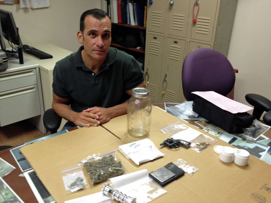 Sgt. Richard Gasparino sitting next to nearly a half pound of cocaine and several ounces of marijuana seized during a raid in the Cove neighborhood on Wednesday evening. Photo: John Nickerson
