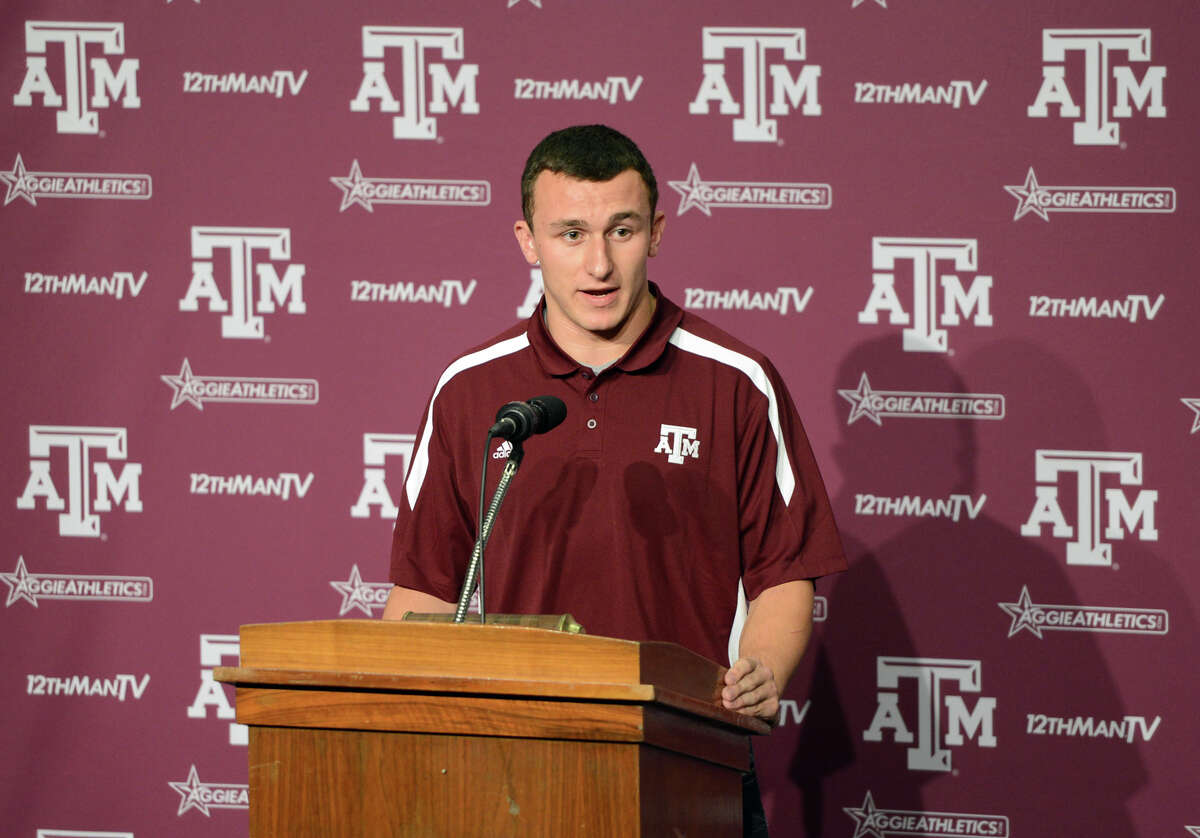 FILE - In this Nov. 27, 2012 file photo, Texas A&M quarterback Johnny Manziel speaks to reporters in College Station, Texas. Manziel didn't speak to the media until late November last year because of coach Kevin Sumlin's ban on freshman talking to reporters. Now he's a sophomore and a Heisman Trophy winner and he's once again being kept from the media. (AP Photo/Bryan-College Station Eagle, Dave McDermand, File)