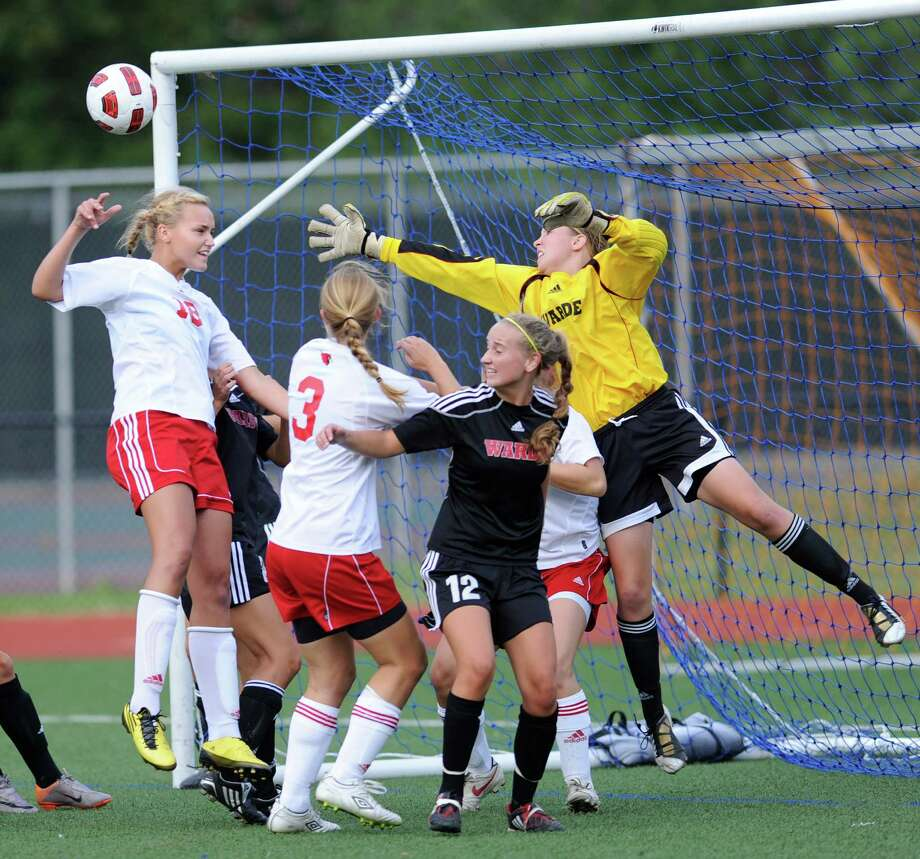 All-FCIAC goalie Katie Brennan, in yellow, reaching for the ball, again backstops a strong Fairfield Warde defense that has the Mustangs expecting big things in 2013. Photo: Bob Luckey / Greenwich Time