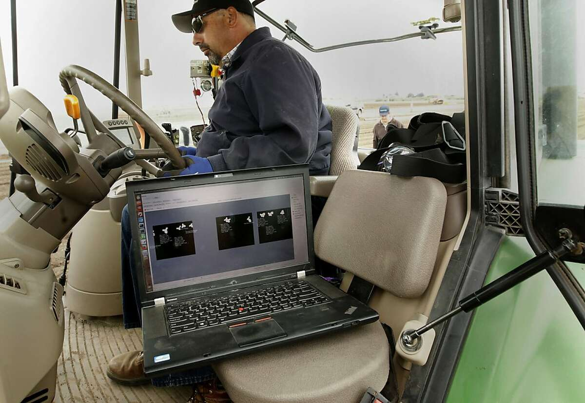 Tractor driver Greg McCready pulls the Lettuce Bot while processing a field in Castroville. A computer shows the position of the 2-week-old romaine lettuce plants under the machine.