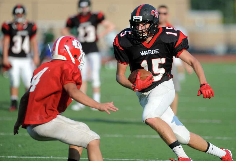 Fairfield Warde's Ryan Brown, right, prepares to make a move against Danbury in an Aug. 27 scrimmage. Wide receiver Brown is expected to be an outside threat for the Mustangs. Photo: Autumn Driscoll / Connecticut Post