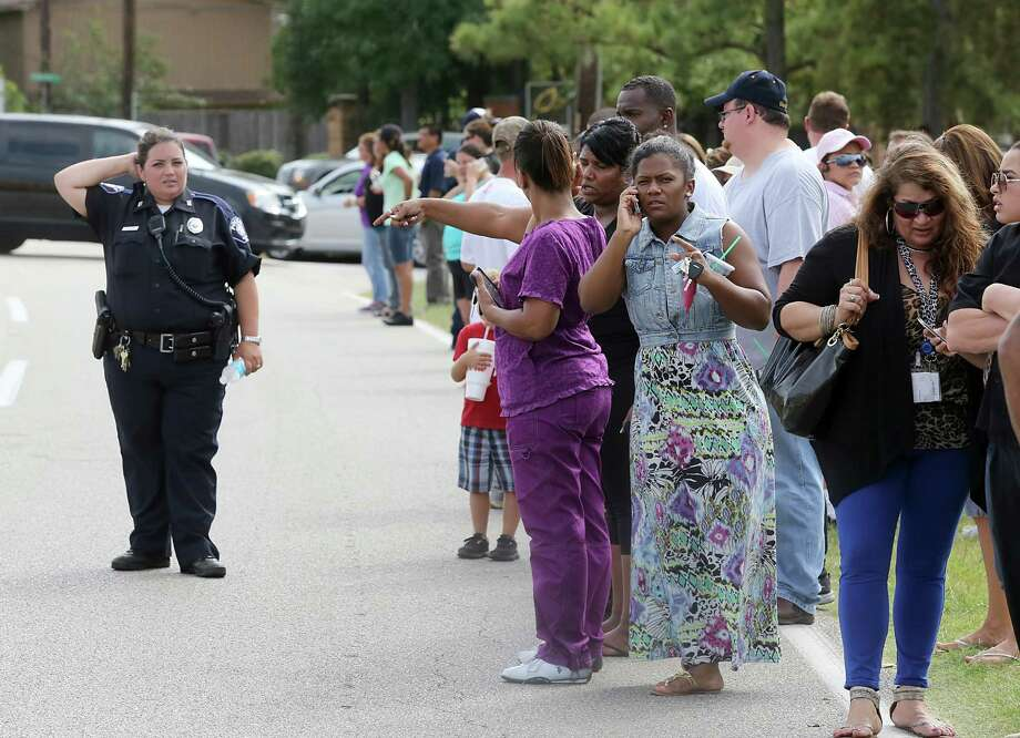 Parents wait across the street from Spring High School for their children to be released from lockdown. Photo: Thomas B. Shea, Stringer / 2013 Getty Images