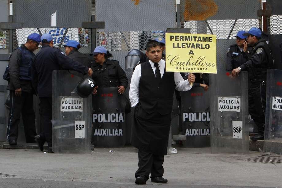 "Mexico: A waiter holds up a sign that reads in Spanish ""Allow me to take you to Cuchilleros Restaurant"" near riot police surrounding the Senate building during a march by unionized teachers in Mexico City. Photo: Marco Ugarte, Associated Press"