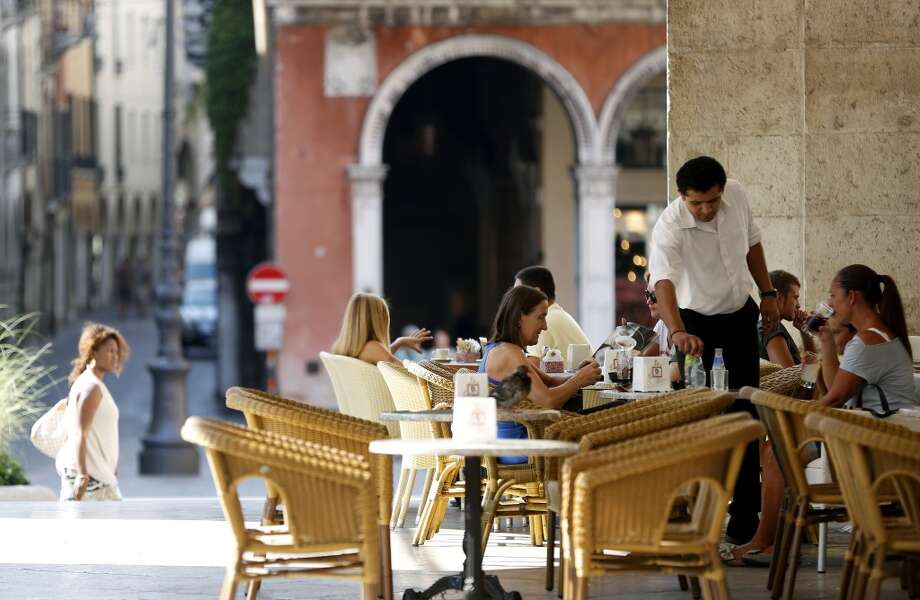 Italy: A waiter serves customers their drinks at an outdoor restaurant terrace in Treviso, Italy,. Italy's Agriculture Ministry has begun to investigate suspected sales of imitation Prosecco sparkling wine in its native Veneto region. Photo: Alessia Pierdomenico, Bloomberg