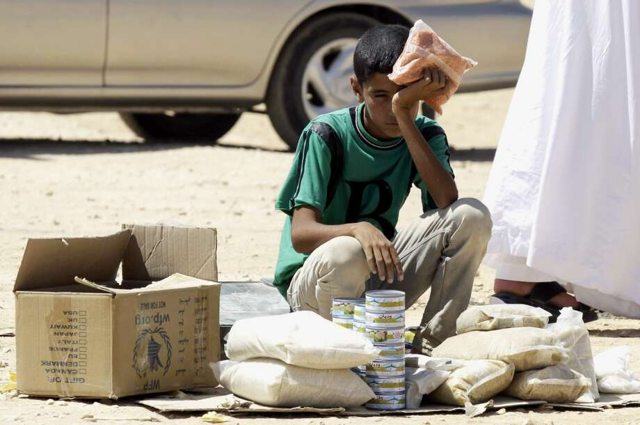 Syria: A young Syrian refugee boy sells canned tuna and other food items in the Zaatari refugee camp, located close to the Jordanian city of Mafraq, near the border with Syria, on September 4, 2013. Photo: Khalil Mazraawi, AFP/Getty Images