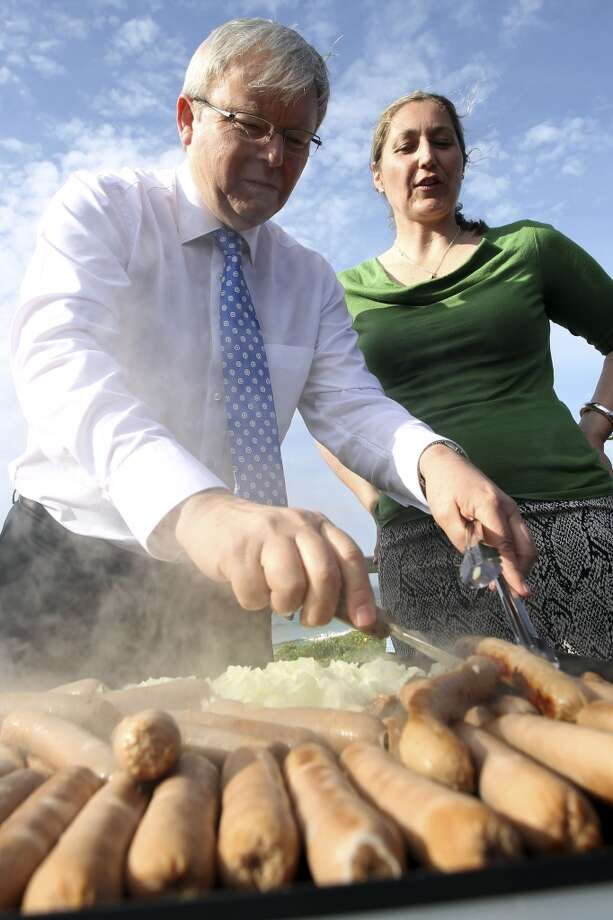 Australia: Australian Prime Minister Kevin Rudd, left, cooks sausages. Photo: Stefan Postles, Associated Press