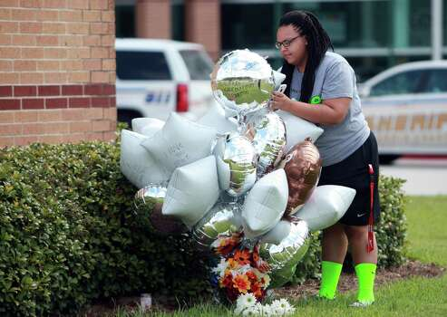 An unidentified person signs a message on a ballon where a memorial for Joshua Broussard is starting to form  outside of Spring High School on Friday, Sept. 6, 2013, in Spring. Photo: Mayra Beltran, Houston Chronicle / © 2013 Houston Chronicle