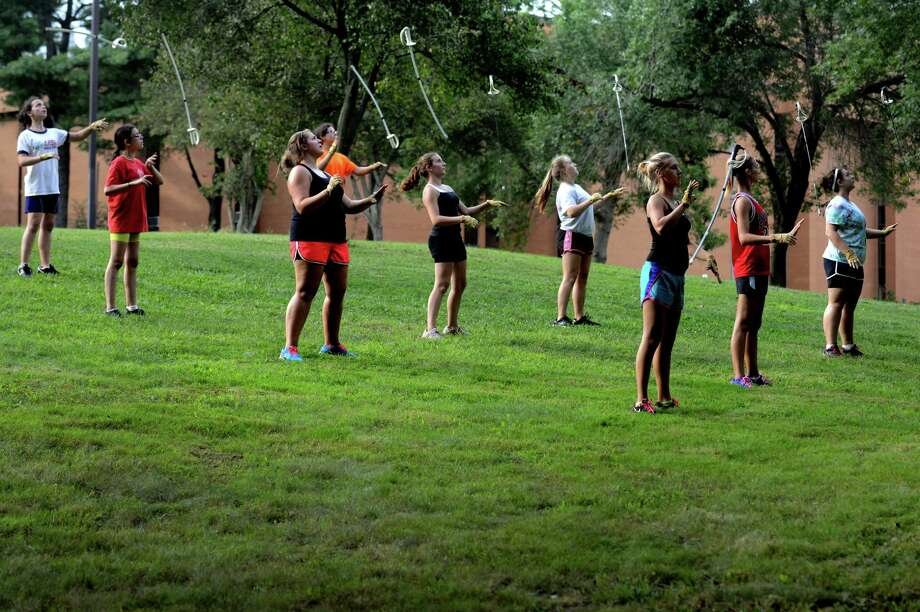 The Shelton High School color guard practices their sword throwing Wednesday, Aug. 28, 2013 in front of the school in Shelton, Conn. Photo: Autumn Driscoll / Connecticut Post