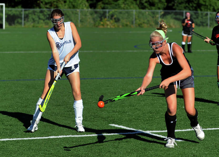 Fairfield Warde's Sarah Adams, right, intercepts the ball during field hockey scrimage action against Staples in Westport, Conn. on Friday September 6, 2013. At left is Staples' Avery Wallace. Photo: Christian Abraham / Connecticut Post