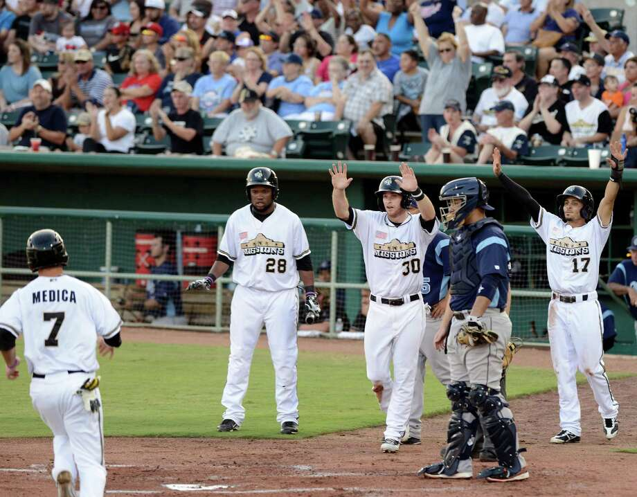San Antonio Missions' Tommy Medica, left, runs home as teammates Yeison Asencio (28), Cory Spangenberg (30), and Rico Noel (17) celebrate behind Corpus Christi Hooks catcher Carlos Corporan, during a Texas League playoff baseball game, Friday, Sept. 6, 2013, at Nelson Wolff Municipal Stadium in San Antonio. (Darren Abate/For the Express-News) Photo: Darren Abate, For The San Antonio Express-News