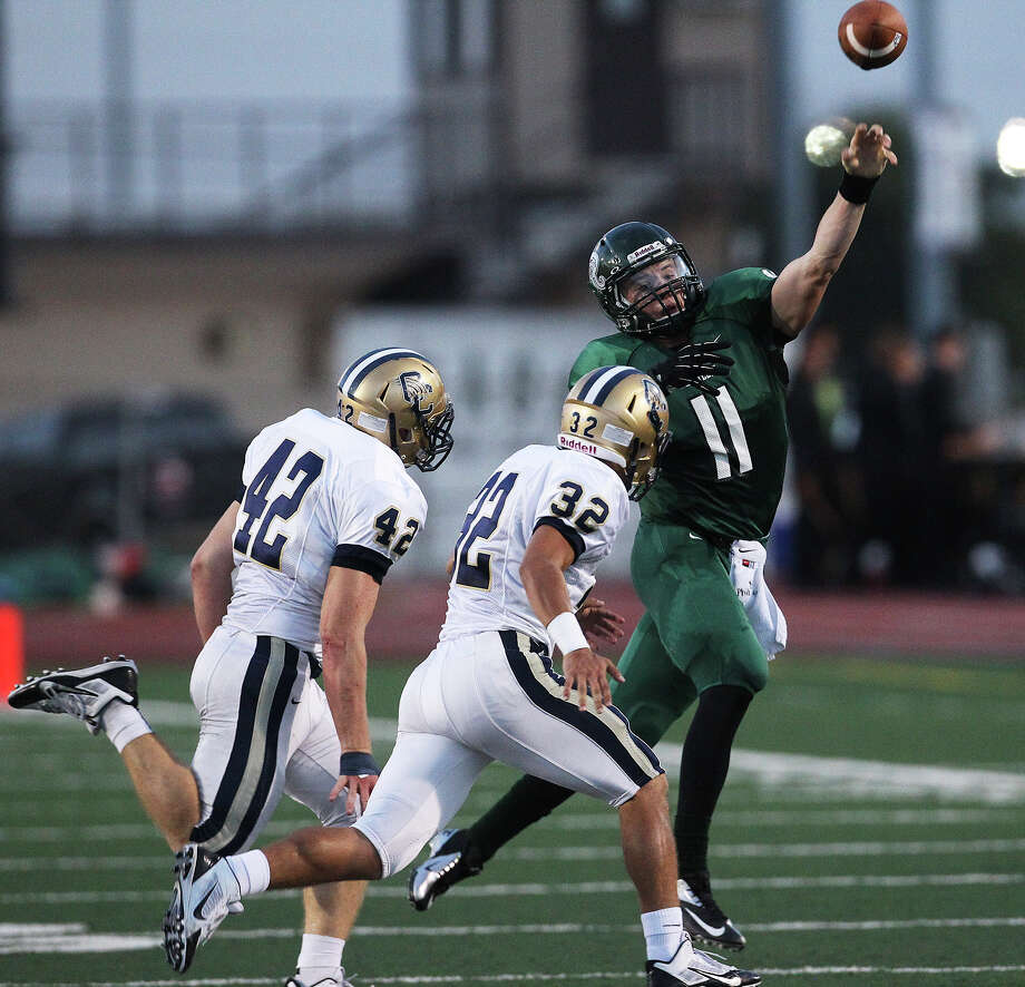 Reagan quarterback Ty Summers (11) throws on the run against O'Connor's Kody Fields (42) and Darren Jasso (32) during their game at Comalander Stadium on Friday, Sept. 6, 2013. Photo: Kin Man Hui, San Antonio Express-News / ©2013 San Antonio Express-News