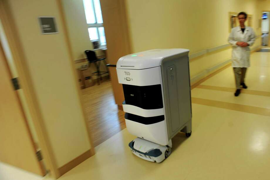 A TUG robot travels down a hallway on Wednesday, Sept. 4, 2013, in Albany Medical Center in Albany, N.Y. Following is Eileen Strosberg, assistant blood bank supervisor. (Cindy Schultz / Times Union) Photo: Cindy Schultz / 00023715A