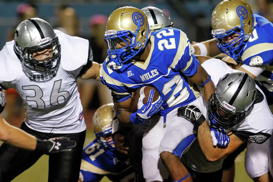 Alamo Heights running back Byron Proctor (center) fights for yardage while being tackled by Clark's Reagan Reyes (right) during the third quarter of their game at Orem Stadium on Friday, Sept. 6, 2013.  Alamo Heights beat the Cougars 47-34.  MARVIN PFEIFFER/ mpfeiffer@express-news.net Photo: Marvin Pfeiffer, San Antonio Express-News / Express-News 2013