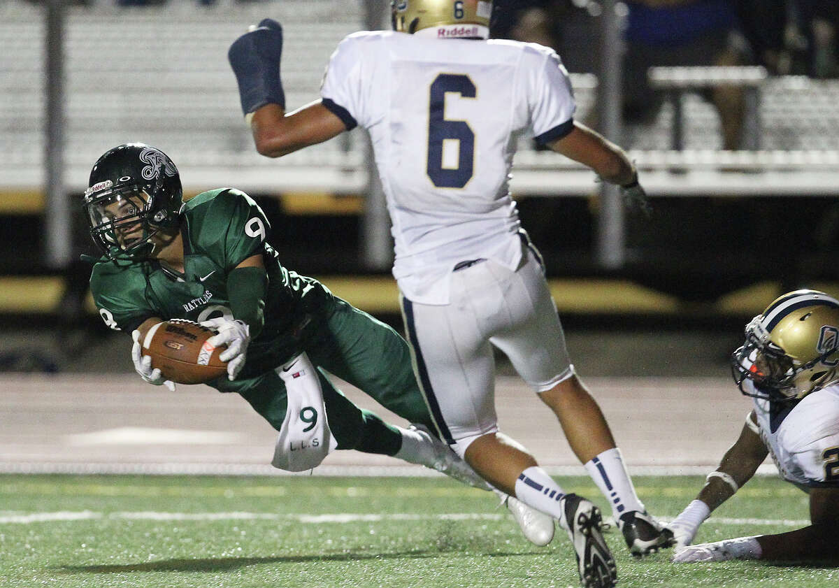 Reagan's Kash Knutson (09) nearly makes a grab at a catch late in the first half against O'Connor's Darryl Godfrey (02) and Reynaldo Zuniga (06) during their game at Comalander Stadium on Friday, Sept. 6, 2013.
