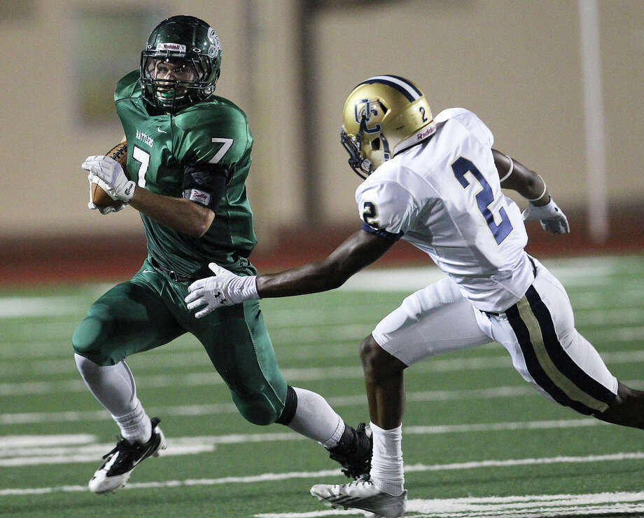 Reagan's Marshall Young (07) runs from O'Connor's Darryl Godfrey (02) during their game at Comalander Stadium on Friday, Sept. 6, 2013. Photo: Kin Man Hui, San Antonio Express-News / ©2013 San Antonio Express-News