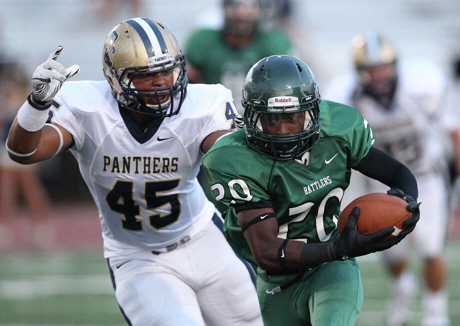 Reagan's Curtis Smith (20) scrambles from O'Connor's Josiah Velazquez (45) during their game at Comalander Stadium on Friday, Sept. 6, 2013. Photo: Kin Man Hui, San Antonio Express-News / ©2013 San Antonio Express-News