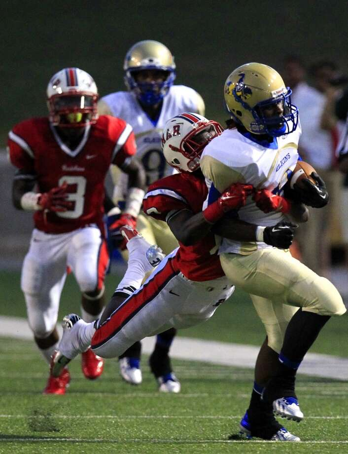 Lamar High School Redskin Trevion Duncan brings down Elkins High School Knight Romanon Skinner during the first half of their matchup at Delmar Stadium, Friday, Sept. 6, 2013, in Houston. (Cody Duty / Houston Chronicle) Photo: Cody Duty, Houston Chronicle