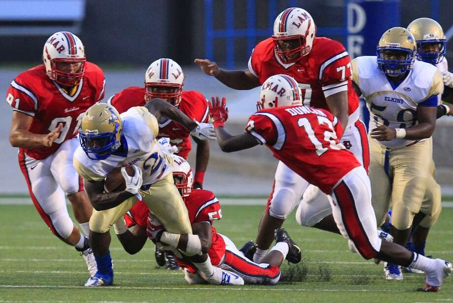 Elkins High School's Timothy Jackson can't shake a pack of Lamar High School defenders during the first half of their matchup at Delmar Stadium, Friday, Sept. 6, 2013, in Houston. (Cody Duty / Houston Chronicle) Photo: Cody Duty, Houston Chronicle