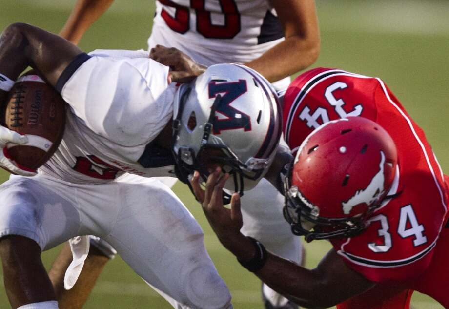 Manvel wide receiver Gary Haynes is tackled by North Shore's John Joseph (34) during the first half of a high school football game on Friday, Sept. 6, 2013, in Galena Park. ( J. Patric Schneider / For the Chronicle ) Photo: J. Patric Schneider, For The Chronicle