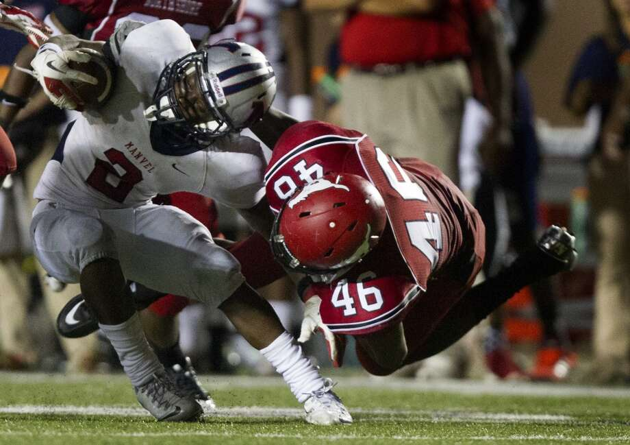 Manvel wide receiver Gary Haynes (2) is taken down by North Shore defensive lineman Dorance Armstrong (46) during the second half of a high school football game on Friday, Sept. 6, 2013, in Galena Park. ( J. Patric Schneider / For the Chronicle ) Photo: J. Patric Schneider, For The Chronicle